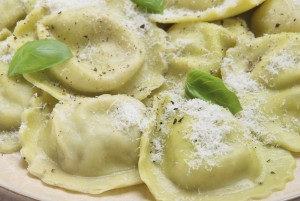 Ravioli with grated Parmesan cheese and basil leaves.